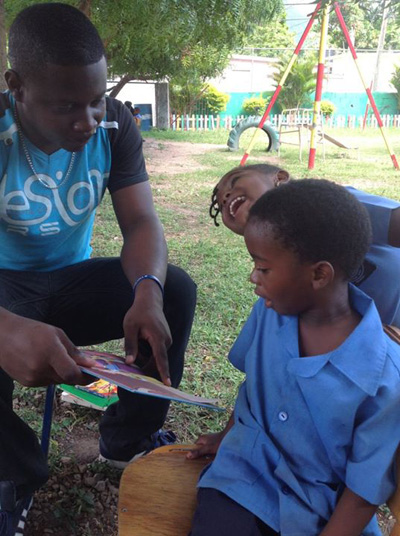 Laroune Francis reads to children at Hermitage Basic School